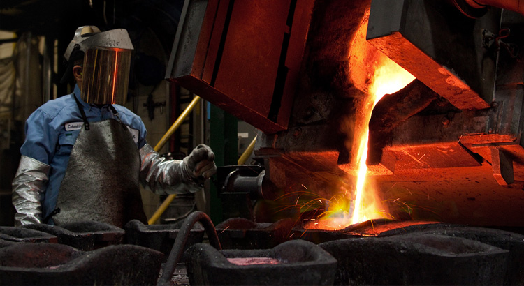 Molten recycled metal being poured by employee