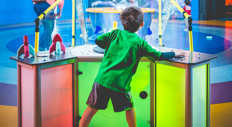 Young boy interacting with exhibit at the museum