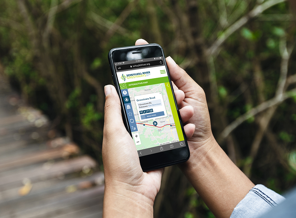 Person holding phone with trail map